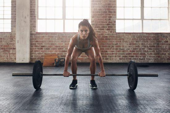 58555063 - female performing deadlift exercise with weight bar. confident young woman doing weight lifting workout at gym.