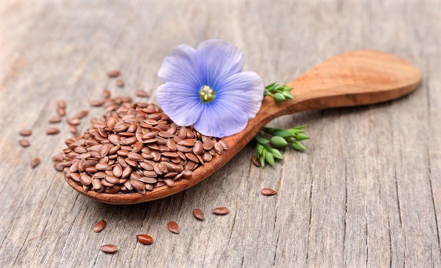 graines de lin dans une cuillère en bois et fleur de lin